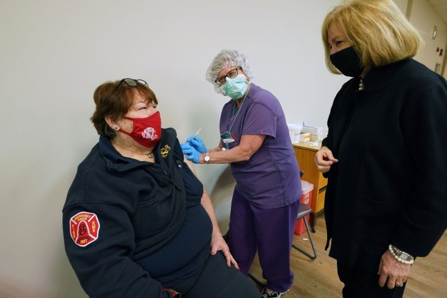 St. Louis Mayor Lyda Krewson (R) visits with an emergency worker on Wednesday as she receives her booster COVID-19 vaccine shot at South City Hospital in St. Louis, Mo. Photo by Bill Greenblatt/UPI