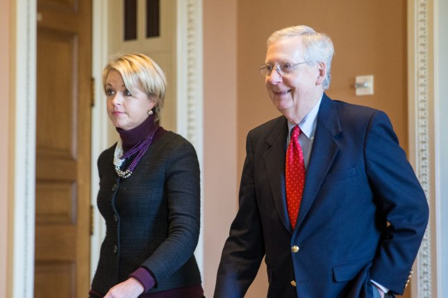 Senate Majority Leader Sen. Mitch McConnell, R-Ky., walks with Stephanie Munchow, Director of Operations for Mitch McConnell, towards the Senate chamber for a vote on a sweeping tax bill in Washington, D.C., on December 1, 2017. Photo by Erin Schaff/UPI