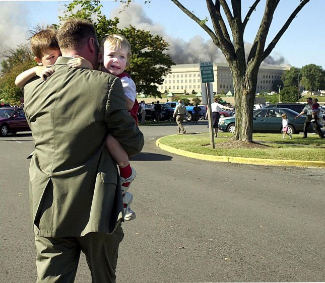 An employee of the Pentagon runs to safety after collecting his children after a hijacked aircraft crashed into the Pentagon on September 11, 2001 in Arlington, Virginia. September 11, 2011 marks the tenth anniversary of the terrorist attacks on the World Trade Center, Pentagon and the crash of flight 93 in Shanksville, Pennsylvania. UPI/Michael Kleinfeld