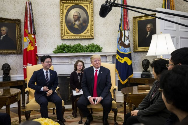 President Donald Trump meets with North Korean defectors in the Oval Office of the White House Friday. During the meeting, Trump said he authorized the full declassification of a controversial memo detailing allegations of misconduct in the FBI. Photo by Zach Gibson/UPI