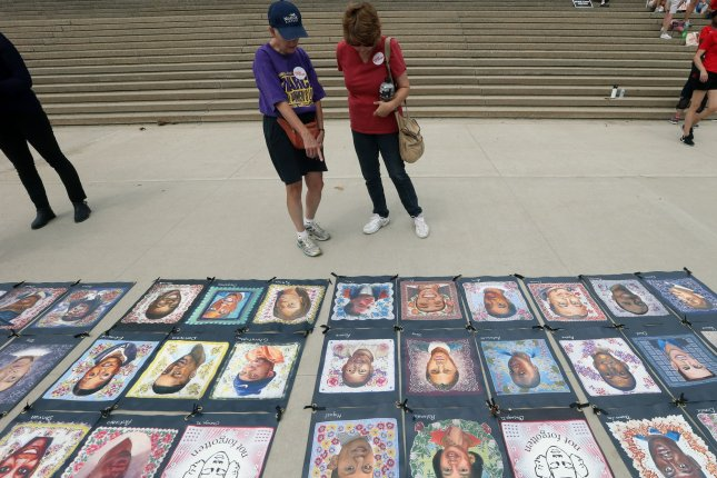Women examine paintings of some of the children who have been killed nationwide by guns underneath the Gateway Arch during a Mom's Demand Action Rally in St. Louis on August 17. File Photo by Bill Greenblatt/UPI