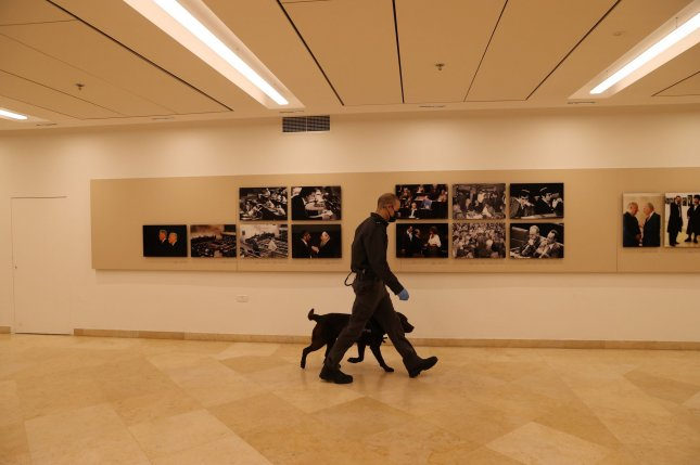A masked security guard and his canine inspect the Israeli Knesset building in Jerusalem, Israel, on December 2. Several members and staffers of the parliamentary body have tested positive for the coronavirus recently. Photo by Alex Kolomoisky/UPI/Pool