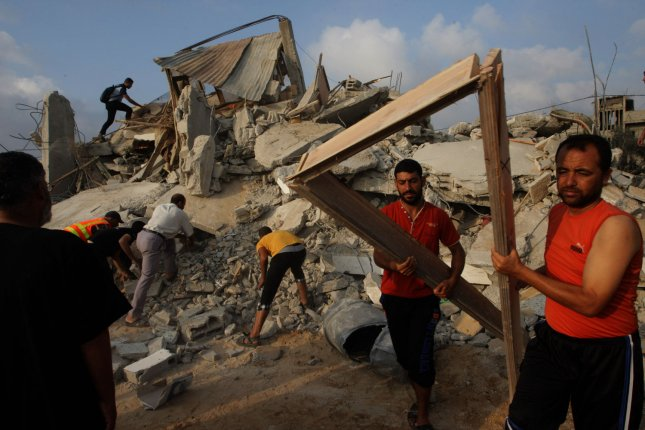 Palestinian rescuers search for victims under the rubble of the Duheir family home, which was destroyed following an Israeli air strike on Rafah in the southern of Gaza strip, on July 29, 2014. More than 100 Palestinians were killed on Tuesday, a day after 10 Israeli soldiers were killed in Gaza. UPI/Ismael Mohamad