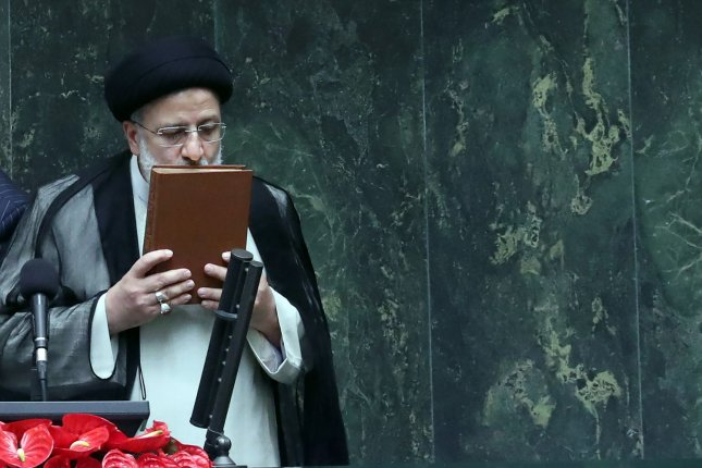 Iranian President Ebrahim Raisi kisses the holy Koran after being sworn in for his first four-year term of presidency at Parliament in Tehran, Iran, on Thursday. Photo by Maryam Rahmanian/UPI