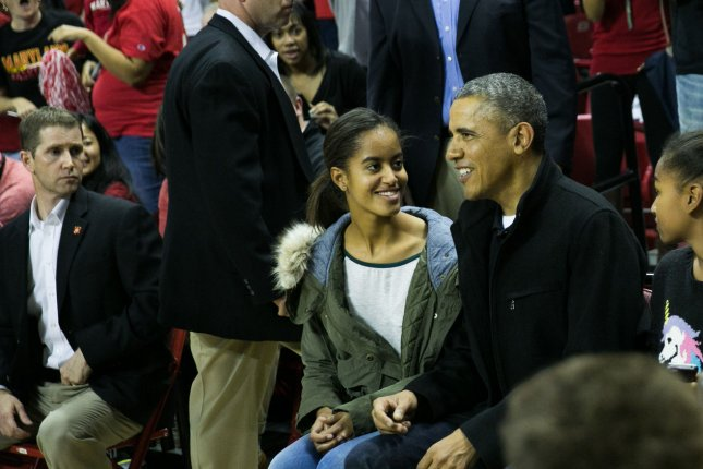 U.S. President Barack Obama talks with daughter Malia Obama as they attend a NCCA basketball game between the University of Maryland and Oregon State University at the Comcast Center in College Park, Maryland on November 17, 2013. Obama's brother-in-law Craig Robinson is the head coach for the Oregon State team. UPI/Drew Angerer/Pool