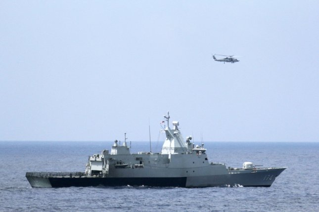 The Royal Malaysian Navy corvette KD Terengganu and a U.S. Navy MH-60R Sea Hawk helicopter from the Blue Hawks of Helicopter Maritime Strike Squadron from the guided-missile destroyer USS Pinckney, conduct a coordinated air and sea search for the missing Malaysian Airlines Flight MH370 jet in the Gulf of Thailand on March 12, 2014. UPI/Claudia Franco/U.S. Navy