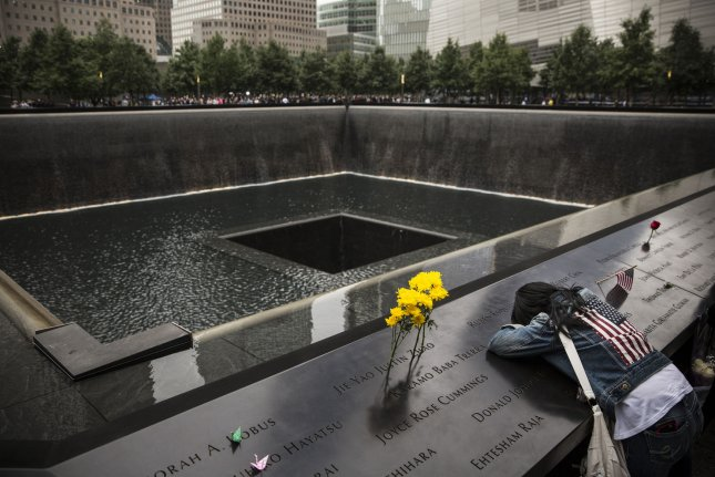 Eileen Esquilin weeps over the name of her brother, Ruben Esquilin Jr, during the memorial observances held at the site of the World Trade Center in New York, September 11, 2014. This year marks the 13th anniversary of the September 11th terrorist attacks that killed nearly 3,000 people at the World Trade Center, Pentagon and on Flight 93. UPI/Andrew Burton/Pool