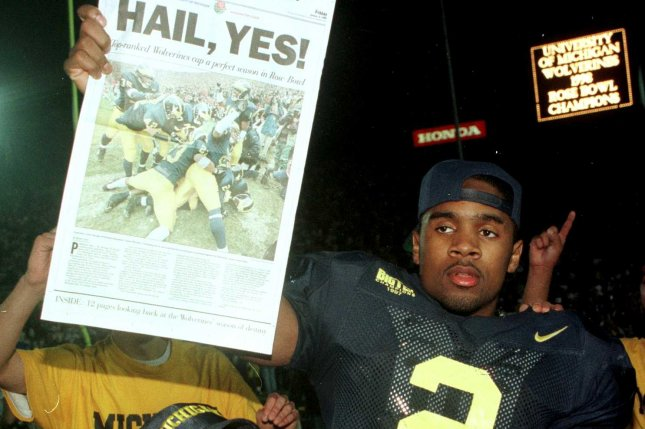 Michigan Wolverines cornerback and Heisman trophy winner Charles Woodson holds up a copy of the Detroit Free Press following the Wolverines' 21-16 defeat of the Washington State Cougars January 1, 1998 at the Rose Bowl in Pasadena, California. File photo by Jim Ruymen/UPI