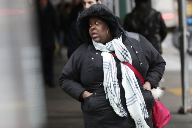 A woman dressed for cold weather walks in lower Manhattan in New York City on January 16, 2019. Temperatures this January are typically warmer in New York and other cities in the east. Photo by John Angelillo/UPI