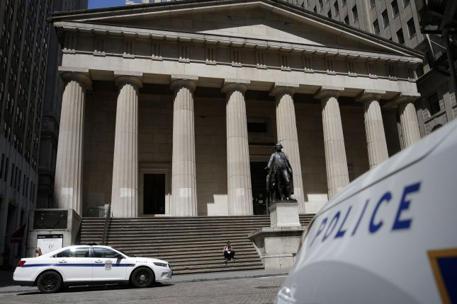 U.S. Park Police vehicles are parked by a statue of George Washington on the steps of Federal Hall before the closing bell on Wall Street in New York City on Friday. Photo by John Angelillo/UPI