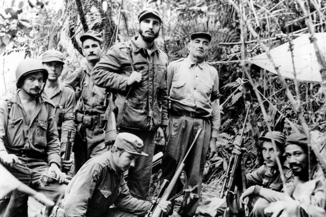 Fidel Castro, leader of Cuba's revolutionary forces, and members of his staff are pictured in the Sierra Maestra mountains on June 7, 1957. From right, Captain Juan Almeida, Captain George Sotus (both seated, right corner), Captain Crescentio Perez, Cuban revolutionary leader Fidel Castro, Captain Raoul Castro, the leader's younger brother (kneeling foreground), Lieutenant Universo Sanchez, Castro's adjutant, Dr. Ernesto Che Guevara, official physician of the rebel army and Captain Guillermo Garcia. (UPI Photo/FILE).