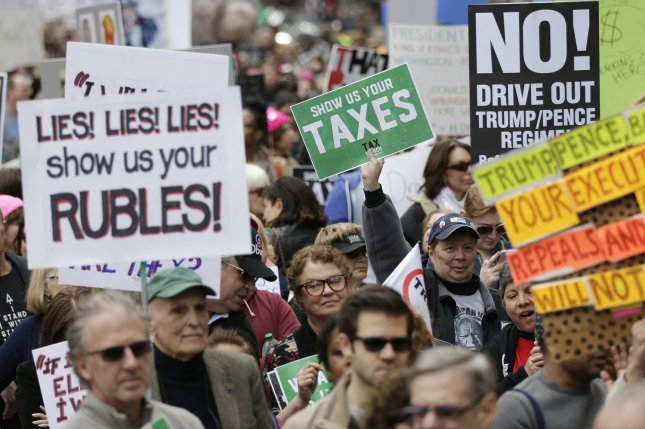 Protesters hold up signs as they participate in a Tax Day protest in New York City on Saturday, April 15, the IRS filing deadline. Protesters across the U.S. took to the streets to demand that Trump make his tax returns public. Photo by John Angelillo/UPI
