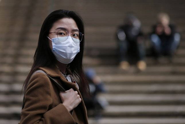 A woman walks near the New York Stock Exchange wearing a face mask on Wall Street in New York City on Tuesday. Photo by John Angelillo/UPI