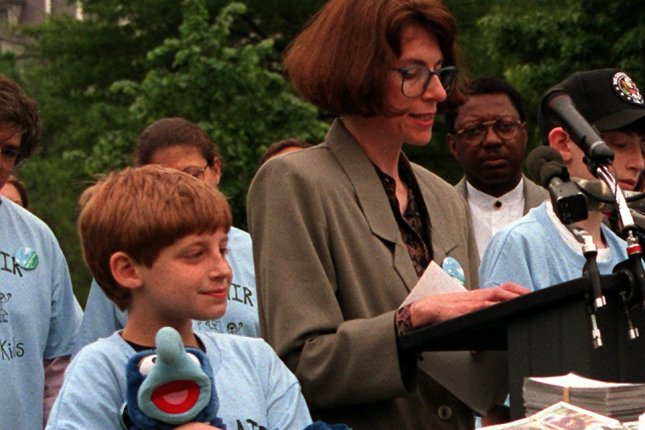 A boy clutches his stuffed animal as his mother, Toby Liebowitz, talks about her children's problems with asthma and calls on President Bill Clinton to enact better clean air laws outside the White House in 1997. (File/Jessica Persson/UPI)