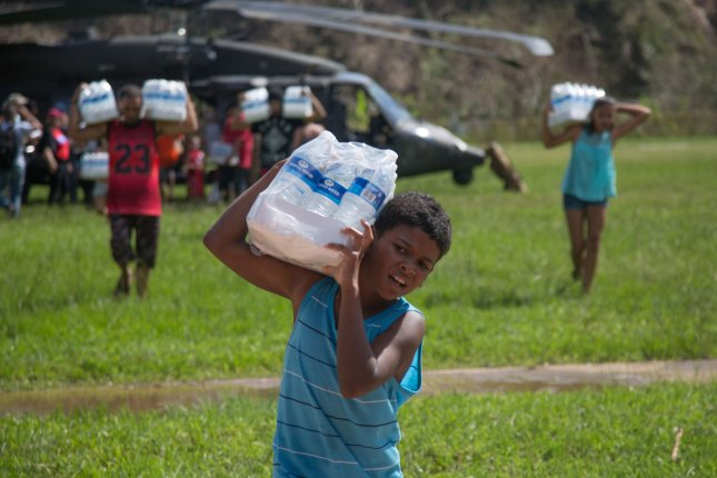 Residents of Jayuga, Puerto Rico, unload food and water from a HH-60 Black Hawk helicopter on October 4, 2017, as part of relief efforts to support FEMA in the recovery process following Hurricane Maria. Photo by Staff Sgt. Pablo Piedra/U.S. Army/UPI