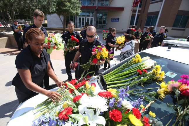 A new Gallup poll found Americans believe societal changes, including a shift in the black community and police operations, can reduce the number of deadly encounters between black men and police. Pictured: Officers with the Dallas Police Department lay flowers on a squad car parked outside headquarters on Lamar Street on July 8 in Dallas, Texas. Four DPD officers and one DART officer were killed and 11 others were wounded after a sniper opened fire during a peaceful Black Lives Matter march late on July 7, 2016. Photo by Chris McGathey/UPI
