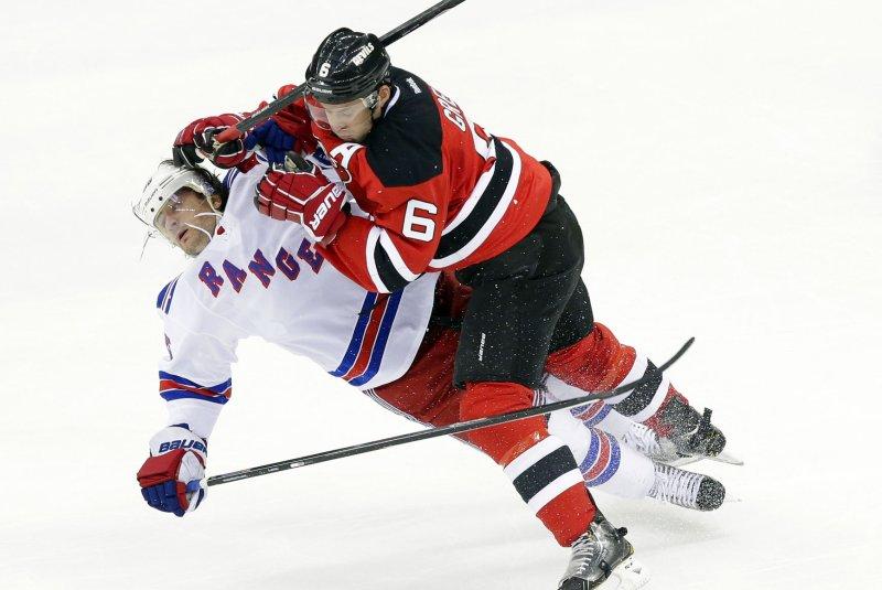 New Jersey Devils' Andy Greene slams New York Rangers' Mats Zuccarello. UPI/John Angelillo
