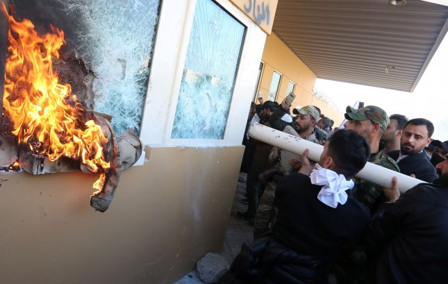 Members of Iraqi Shiite Popular Mobilization Forces armed group and their supporters attack the entrance of the U.S. Embassy, in Baghdad, Iraq, on Dec. 31, 2019. Photo by Humam Mohamed /UPI
