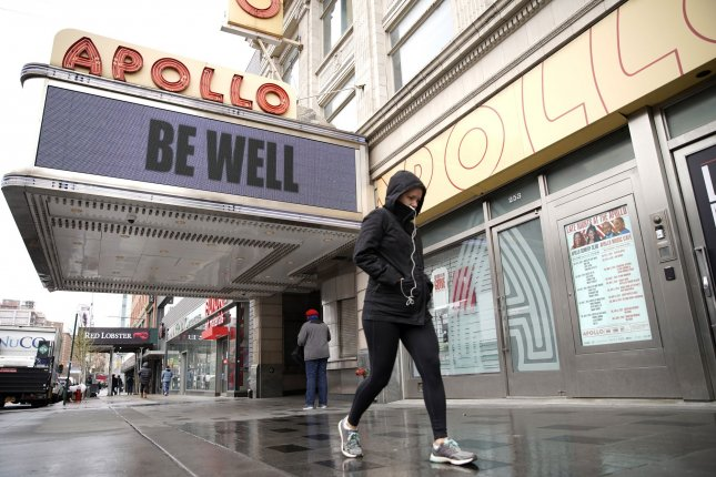 Pedestrians walk by the Be Well message on the Apollo Theater marquee in the Harlem section of New York City on Friday. Photo by John Angelillo/UPI