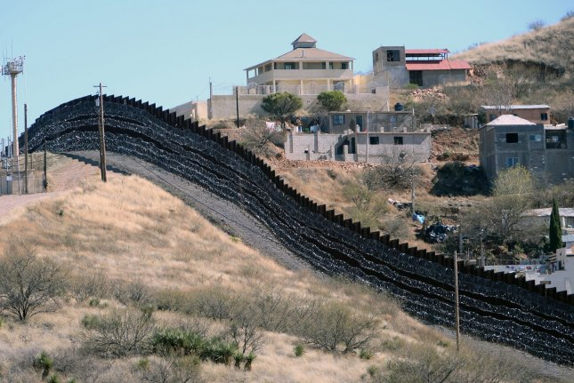 Barbed wire has been placed on top and side of the fence along the United States-Mexico border, shown here, heading East from Nogales, Arizona, in February 2019. The Department of Defense has awarded $524 million to Southwest Valley Constructors to build sections of the border wall near Tucson, Ariz. Photo by Art Foxall/UPI