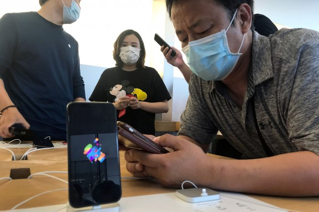 Shoppers visit an Apple store in Beijing, China, on June 7. A top analyst said Monday the company sold about 2 million iPhone 12s in the first 24 hours of orders. File Photo by Stephen Shaver/UPI