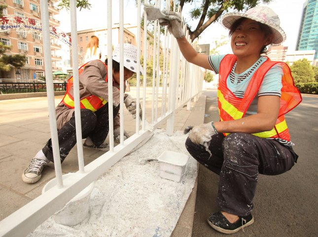 WHO: Lead paint causes 600,000 cases of intellectual disabilities a year. Chinese migrant workers put a new coat of white paint on pedestrian barriers lining a street in Beijing. UPI/Stephen Shaver