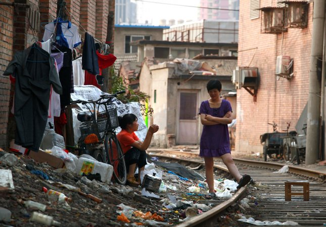 Chinese women sit outside their low-income apartment next to train tracks in Beijing on July 3, 2013. The United Nations has singled out China - the world's most populous country, with over 1.3 billion people - as one of the key success stories in its longstanding battle against poverty. However, extreme poverty rates still exist across much of the country. UPI/Stephen Shaver