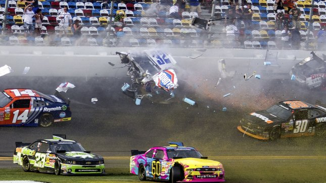 Spectators duck and shield themselves from debris from Kyle Larson's #32 Clorox Chevrolet as it disintegrates from a wreck on the way to the finish line on the final lap of the NASCAR Nationwide Series DRIVE4COPD 300 auto race at Daytona International Speedway in Daytona Beach, Florida February 23, 2013. Spectators were injured in the stands. UPI/Mark Wallheiser