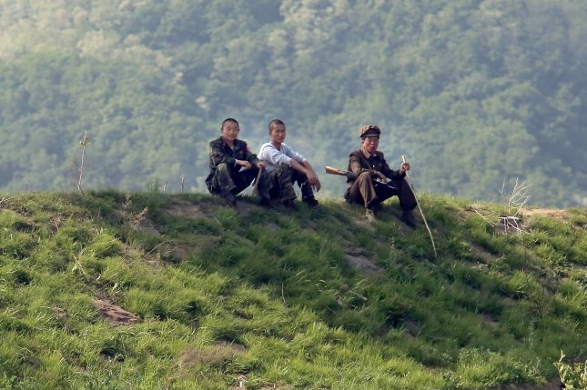 "North Korean soldiers sit in the shade near the North Korean city Sinuiju, across the Yalu River from Dandong, China's largest border city with North Korea. Kim Jong Un's frequent replacement of top-ranking military officers is an indication the leader is phasing out Songun, or ""military-first"" policies that were in place in the 90s. Photo by Stephen Shaver/UPI"