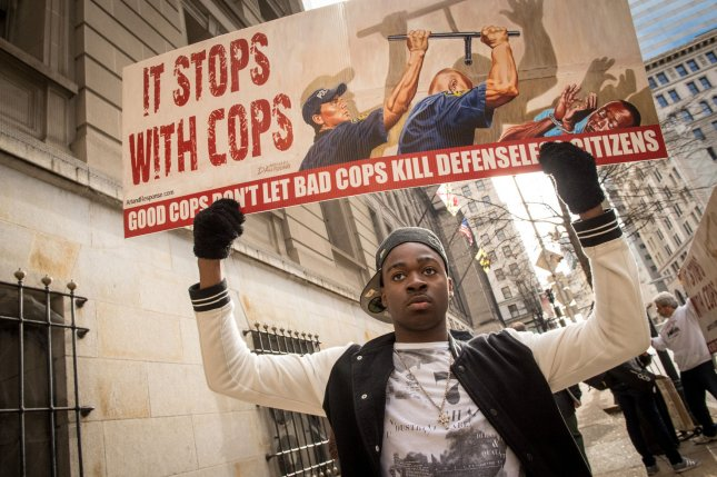 Melvin Townes holds up a sign in front of the city courthouse during the trial against Baltimore police Officer William Porter in Baltimore on Wednesday. A mistrial was declared. Photo by Ken Cedeno/UPI
