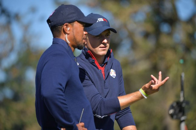 Tiger Woods, shown here talking with Team USA member Jordan Spieth during the Ryder Cup last fall, has been spending more time on course design during his down time after back surgery. File photo by Kevin Dietsch/UPI