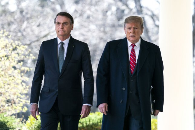 U.S. President Donald Trump walks at the White House with Brazilian President Jair Bolsonaro on March 19, 2019. Bolsonaro's press secretary, who also traveled to Trump's Florida resort last weekend, has tested positive for the coronavirus. File Photo by Jim Lo Scalzo/UPI