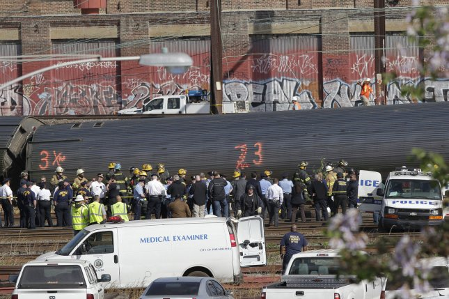 A Medical Examiner truck pulls up to where Police, emergency and rescue workers surround the car of an Amtrak train that crashed on May 13, 2015 in Philadelphia. At least six people were killed and over 140 people hurt after the Amtrak train, carrying 238 passengers and five crew members, derailed and rolled onto its side in the Port Richmond section of Philadelphia Tuesday night. All seven cars of Amtrak Northeast Regional Train 188 derailed and came off the tracks near Frankford Junction shortly after 9 p.m. on Tuesday Night. Photo by John Angelillo/UPI