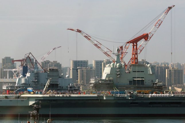China's two aircraft carriers, one purchased from Ukraine in 2012 and one domestically built (background), are moored in a shipyard as they undergo modifications in Dalian, a major Chinese port city in Liaoning Province, on July 19, 2018. File Photo by Stephen Shaver/UPI
