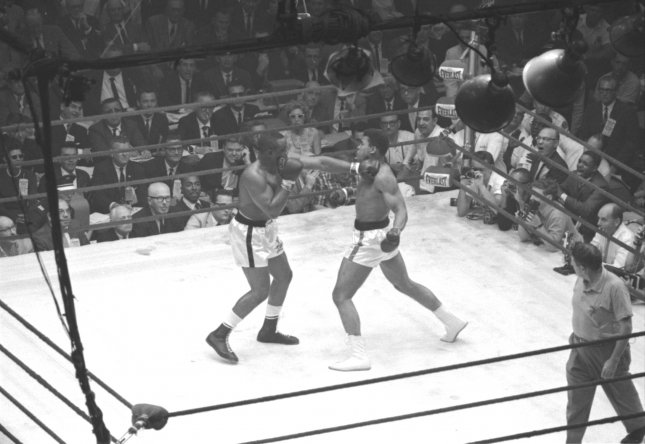 Cassius Clay (R) battles Sonny Liston in a Miami Beach, Fla., world heavyweight championship fight that shook the boxing world Feb. 25, 1964. Brash underdog Clay (who became Muhammad Ali) won the title. File Photo/UPI