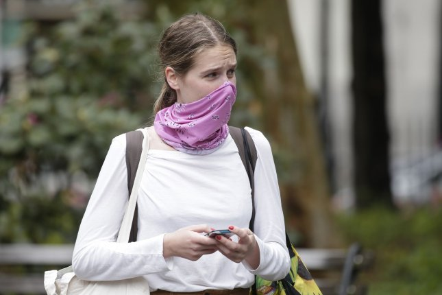 A woman wears a protective face mask in New York City on Friday. Gov. Andrew Cuomo said Saturday that nearly 300 people died in the previous 24 hours in the state. Photo by John Angelillo/UPI