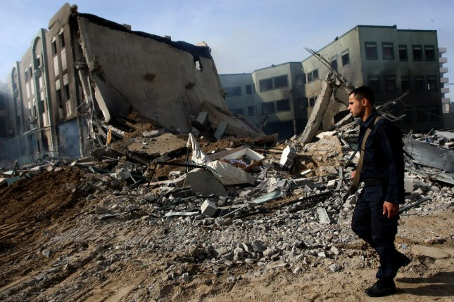 Hamas security members inspect a destroyed Ministry of Interior building after an Israeli air strike in Gaza City on November 16, 2012. Missiles continue to be fired on Israeli targets by Palestinian militants in the Gaza Strip, as Israel continues to strike targets inside the Gaza Strip, on the second day of Operation Pillar Cloud, following the assassination of Hamas militant leader Ahmed Jabari. Israeli forces launched a heavy barrage of bombs at the break of dawn but also announced a three hours ceasefire during the visit of the Egyptian Prime Minister Hisham Qandil in the Gaza Strip. UPI/Ismael Mohamad