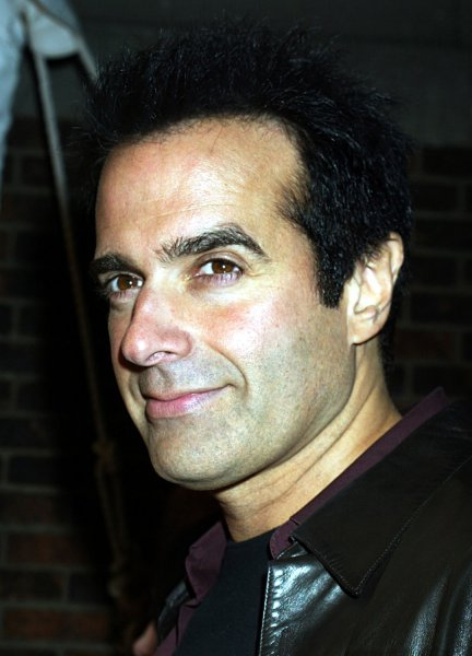 David Copperfield poses for pictures at the Victoria's Secret fashion show in New York City on November 13, 2003. (UPI Photo/John Angelillo)