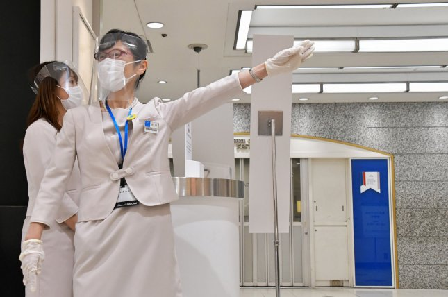 An employee wears a face shield and face masks at the Matsuya Ginza department store, which partially reopened Monday in Tokyo. Photo by Keizo Mori/UPI