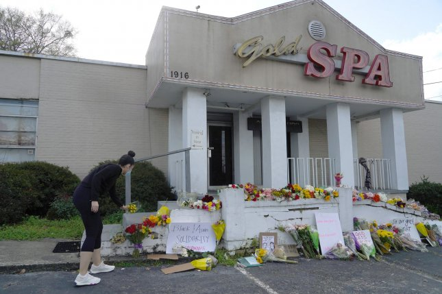Attacks on Asian Americans have increased more than 150% during the past year. A woman lays flowers at a makeshift memorial Thursday outside the Gold Spa, one of the sites of deadly shootings that killed eight people, in Atlanta, Georgia. Photo by Tami Chappell/UPI