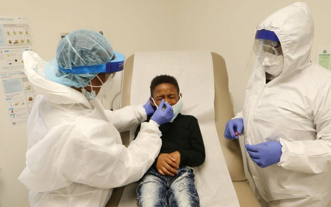 Eight year-old Kayden Tree grimaces as a swab is inserted into his nose by nurse Nellie Smith (L) and Ebonie Hearn, during a COVID-19 test at a CareSTL Health testing Site in St. Louis in May 2020. File Photo by Bill Greenblatt/UPI
