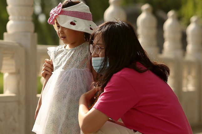 A mom walks with her daughter along a lake in Beijing on Tuesday. China says it will allow couples to have three children, up from two, as the Communist Party attempts to reverse declining birthrates and aver a population crisis, but experts say it is woefully inadequate. Photo by Stephen Shaver/UPI