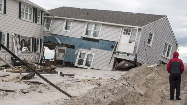A passerby looks over a destroyed beach front home November 1, 2012 that was ripped apart by high winds and water on Long Beach Island October 29, 2012. Many homes on this resort New Jersey island were destroyed when Hurricane Sandy hit the area. UPI/John Anderson