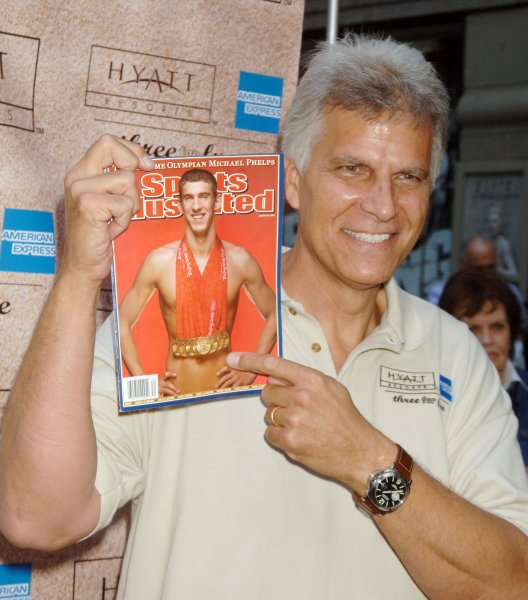 Mark Spitz, who won the last of his seven swimming gold medals in the Olympics in Munich, Germany, on Sept. 4, 1972, holds a Sports Illustrated cover Aug. 20, 2008, featuring fellow American swimmer Michael Phelps, who broke Spitz's longstanding record with eight golds in the 2008 Games in Beijing. File Photo by Ezio Petersen/UPI