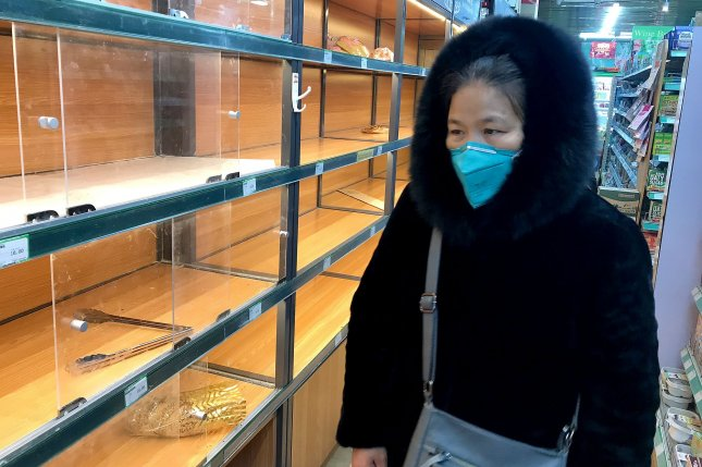 A woman is seen at a store with mostly empty shelves on Thursday as panic buying is starting to hit certain areas due to the threat of the coronavirus in Beijing, China. Photo by Stephen Shaver/UPI
