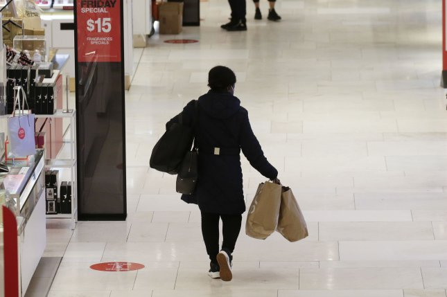 A shopper holding bags walks through a retail store in Herald Square in New York City on Friday. For over a decade, Black Friday has traditionally been the official start to the busy buying binge sandwiched between Thanksgiving and Christmas. Photo by John Angelillo/UPI