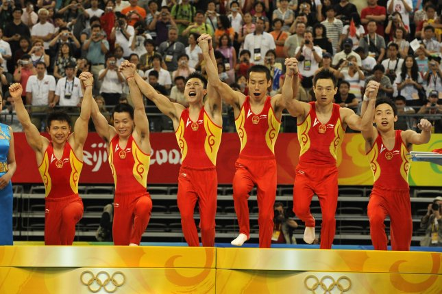 The Chinese men's gymnastics team join hands and run to the stage to receive their gold medals after winning the men's team final, at the National Indoor Stadium, August 12, 2008, at the Summer Olympics in Beijing, China. (L-R) Chen Yibing, Huang Xu, Li Xiaopeng, Xiao Qin, Yang Wei and Zou Kai. The Japanese won the silver and the U.S. won the bronze. (UPI Photo/Mike Theiler)
