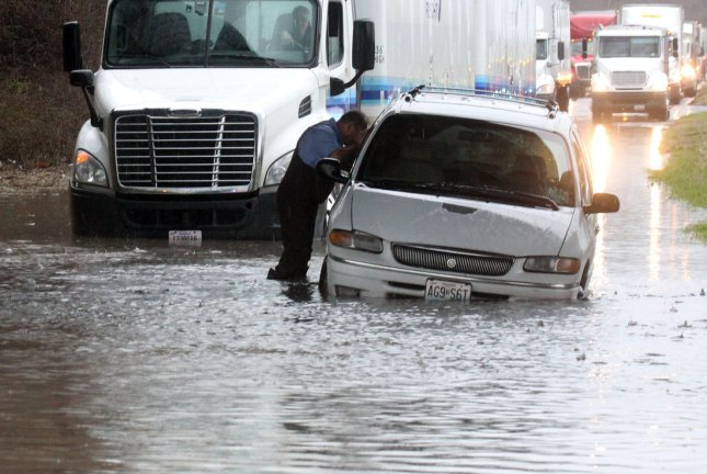 A St. Louis firefighter checks a vehicle for occupants after it was left abandoned on a flooded road in St. Louis on April 2. 2014. Heavy, all-day rains have flooded many area roads in low areas near the Mississippi River. Three cars were stranded in this area north of the city but no injuries were reported. UPI/Bill Greenblatt
