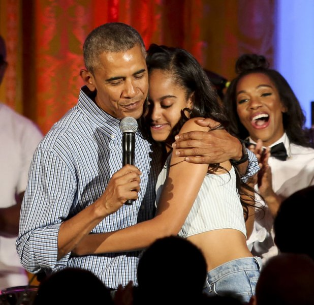 President Barack Obama hugs his daughter Malia, after singing Happy Birthday to her at the Fourth of July White House party, while singer Janelle Monáe (R) reacts on July 4, 2016 in Washington, DC. Malia was born 18 years ago. Pool photo by Aude Guerrucci/UPI