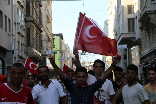 People wave Turkish flags during a demonstration in support of the Turkish president in Istanbul, Turkey, on July 16, 2016 following an attempted military coup. Turkey's trade minister estimated the cost of the coup to the economy at $100 billion Monday. Photo by Hanna Noori/ UPI